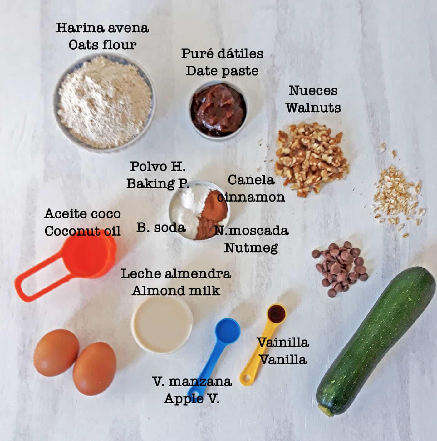 ingredientes para preparar muffins de zucchini sobre una mesa blanca