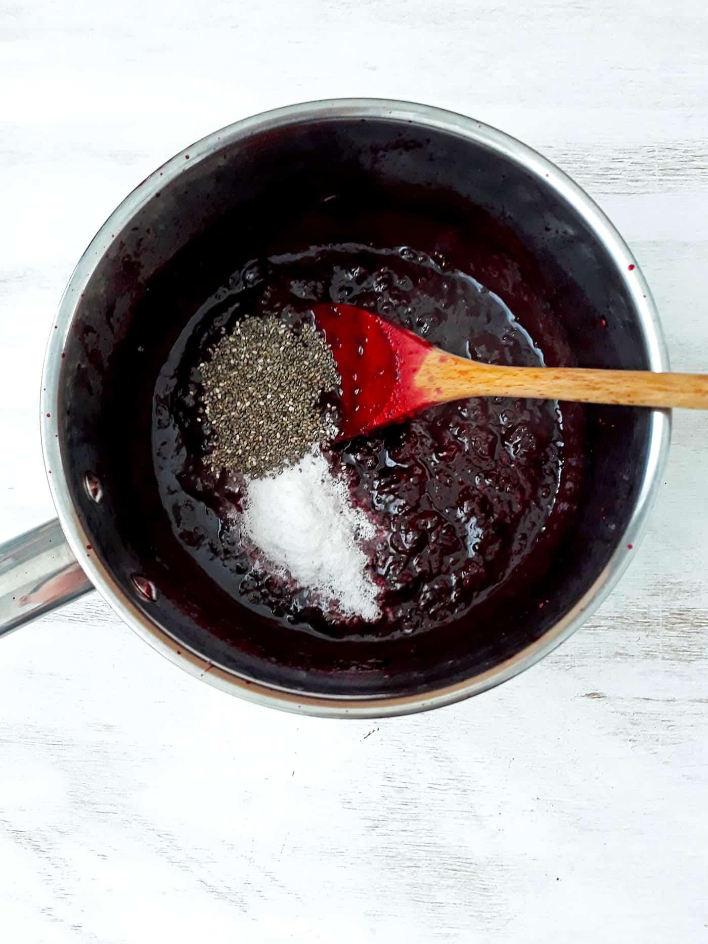 mermelada de frutos rojos en una olla con semillas de chía stevia y una cuchara de palo