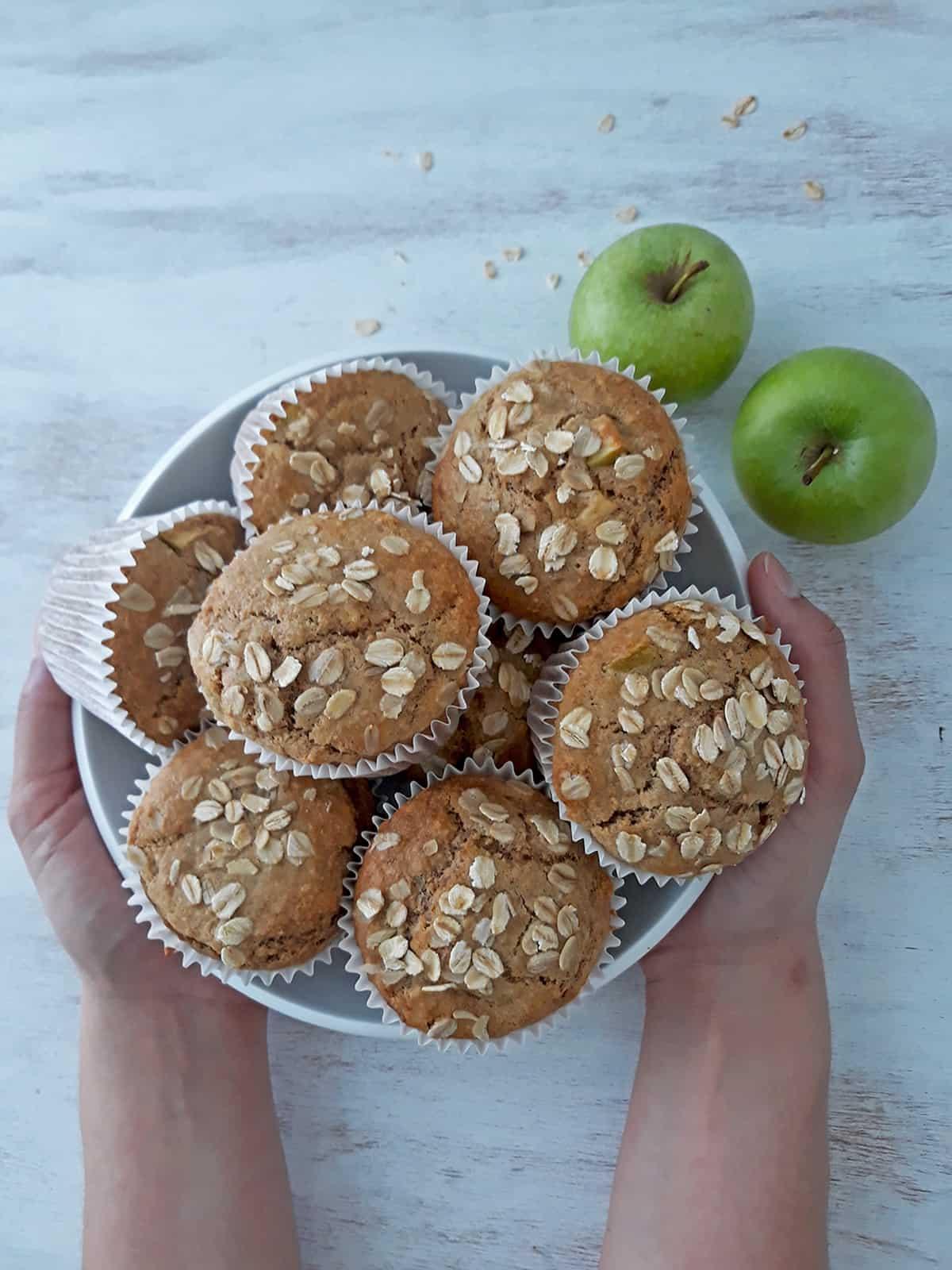muffins de manzana en un contenedor blanco con dos manzanas frescas