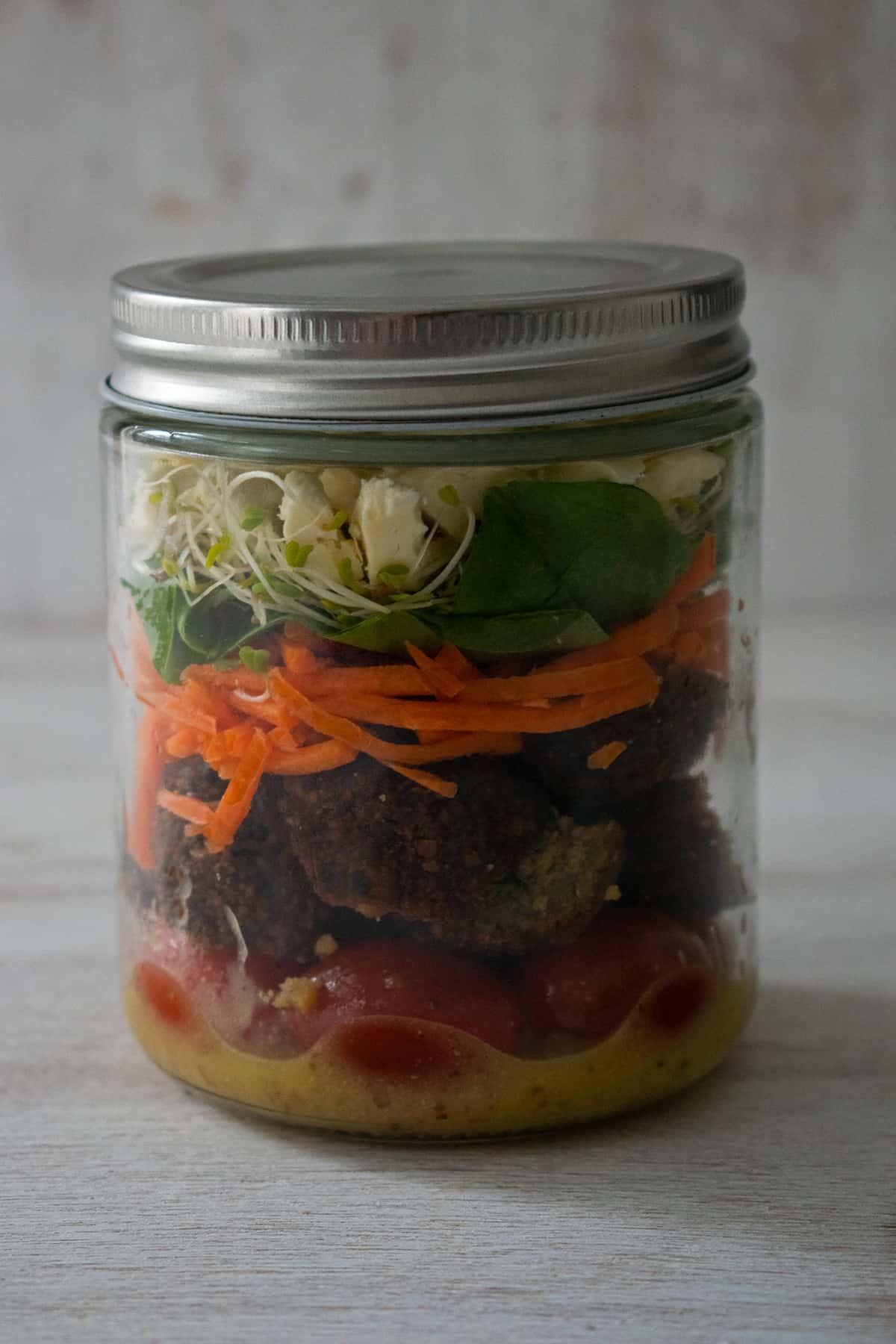 ensalada de falafels en un frasco de vidrio