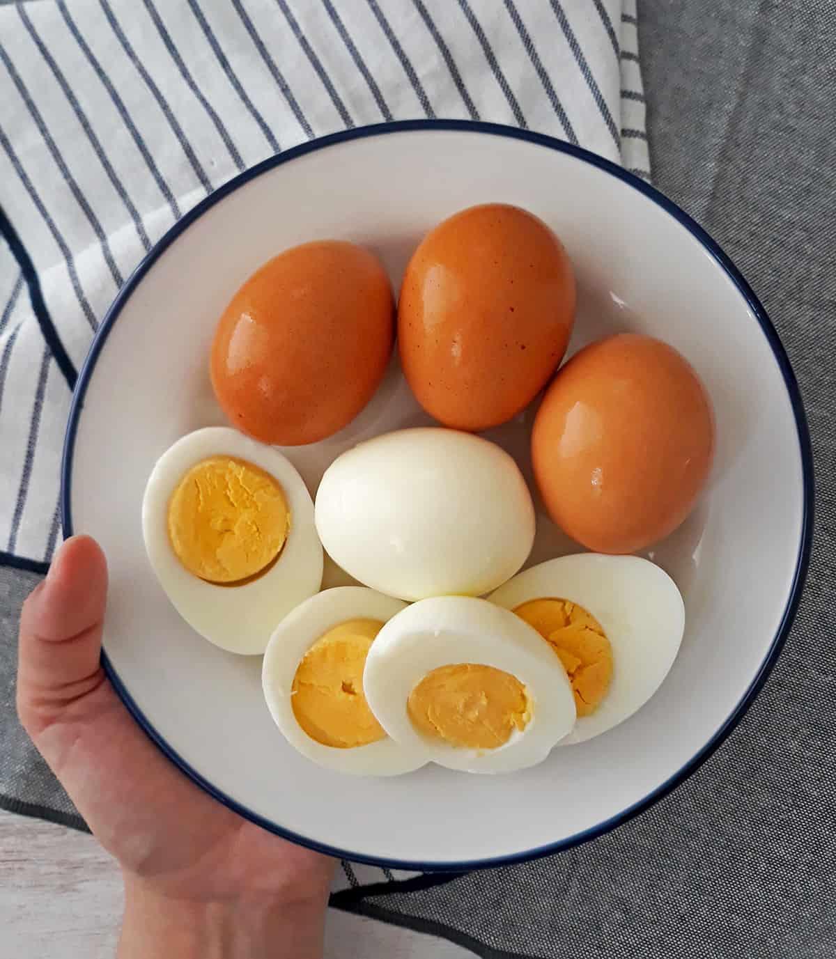 huevos duros con cascara y sin cascara en un plato