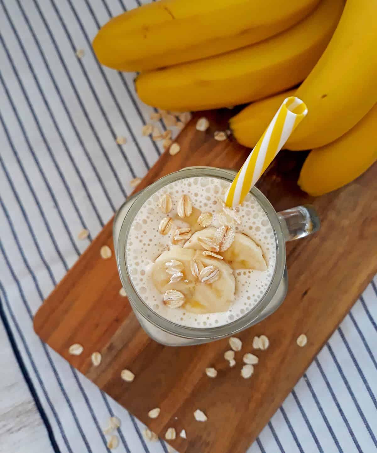 smoothie de banana con un pitillo amarillo y blanco y bananas frescas