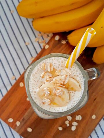smoothie de banana con un pitillo amarillo y blanco acompañado de bananas