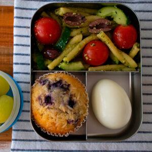 lonchera con ensalada de pasta, muffin, huevo duro y uvas