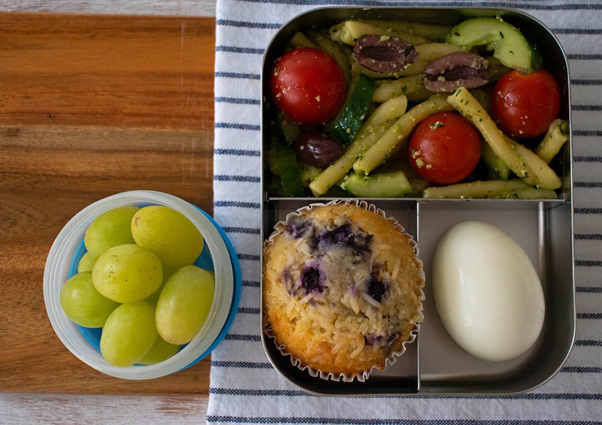 lonchera con ensalada de pasta pesto, muffin y uvas