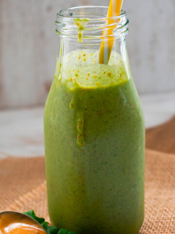 smoothie verde servido con una cuchara de mantequilla de maní