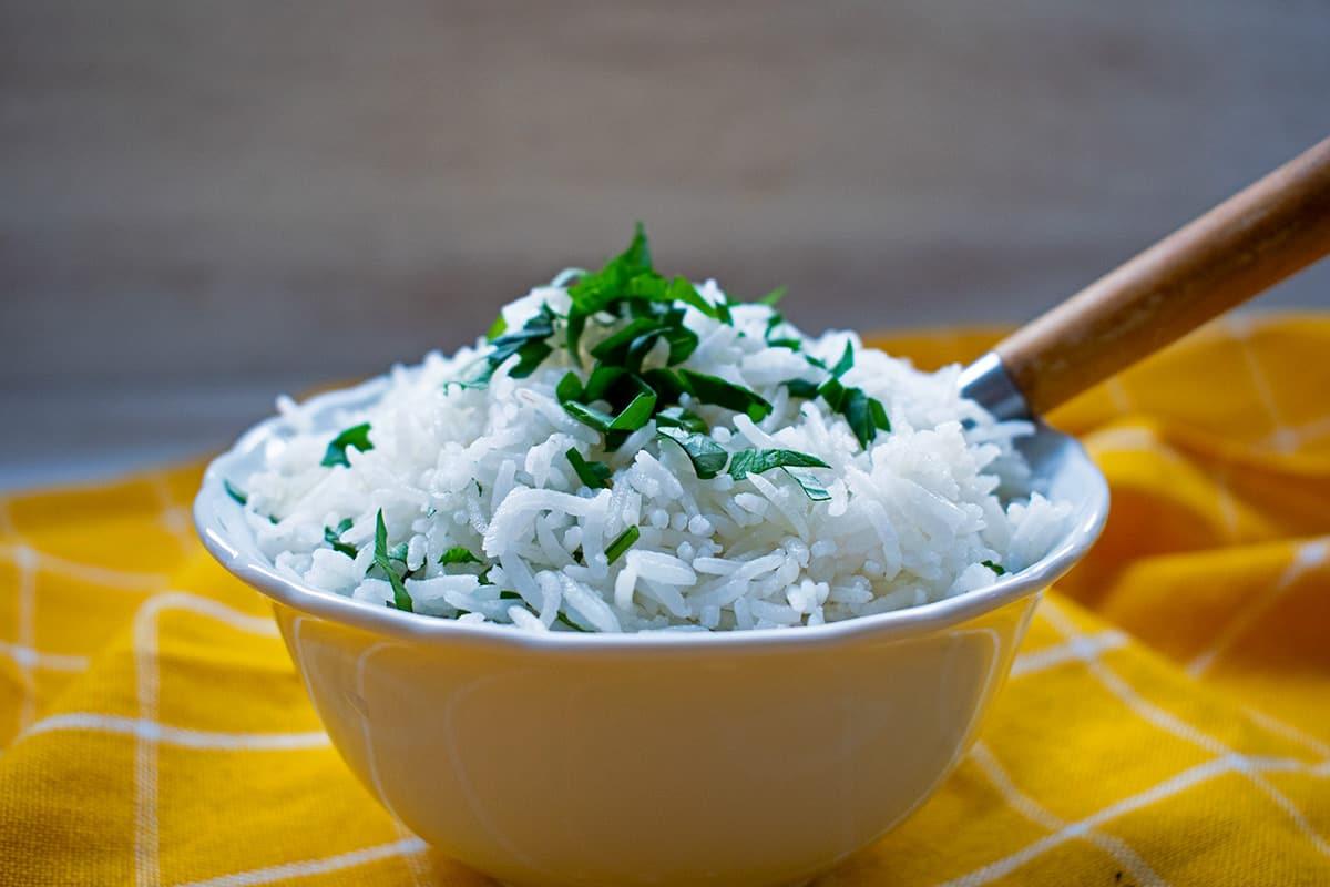 arroz blanco en un bol blanco con una cuchara de madera