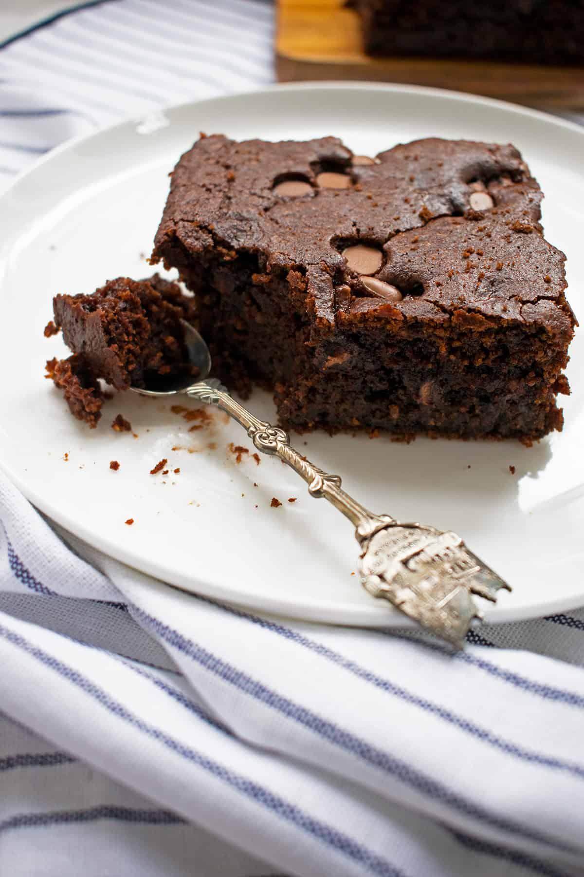 brownie de chocolate servido en un plato blanco con una cuchara pequeña
