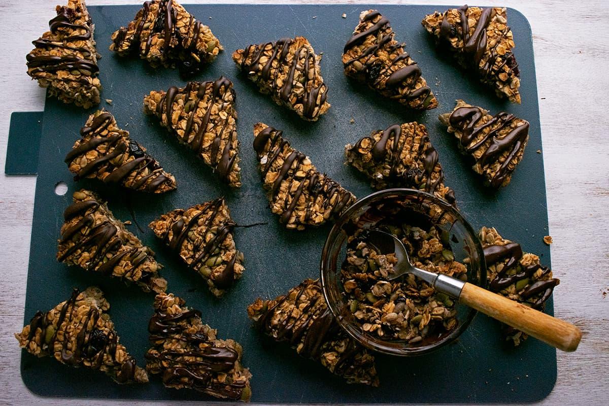 barritas de avena con chocolate derretido por encima sobre una tabla para cortar.