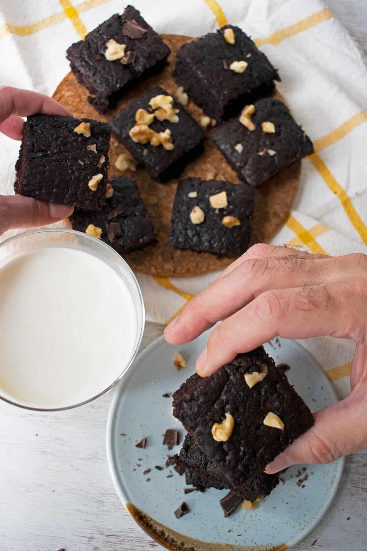 brownies sobre una mesa con un vaso de leche, las manos de dos personas cogiendo algunos de los brownies.