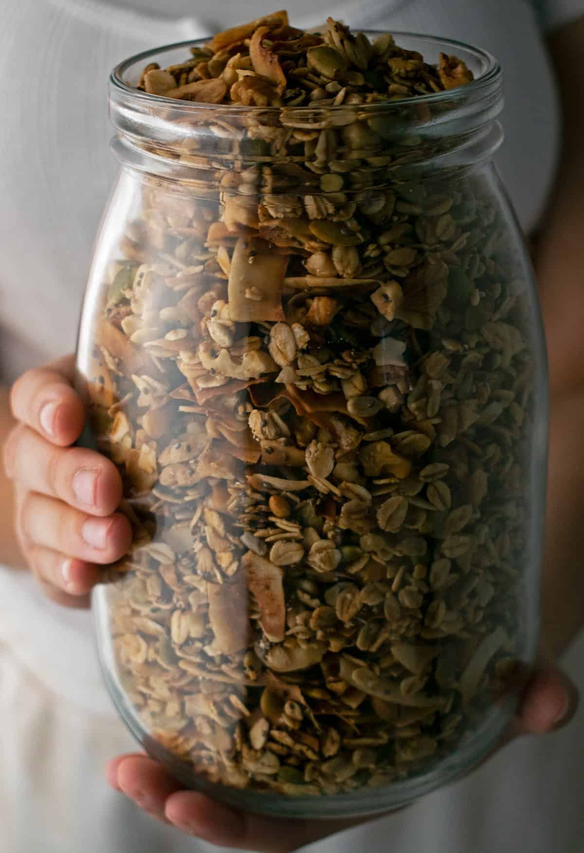 granola en un frasco de vidrio sostenido por las manos de una mujer