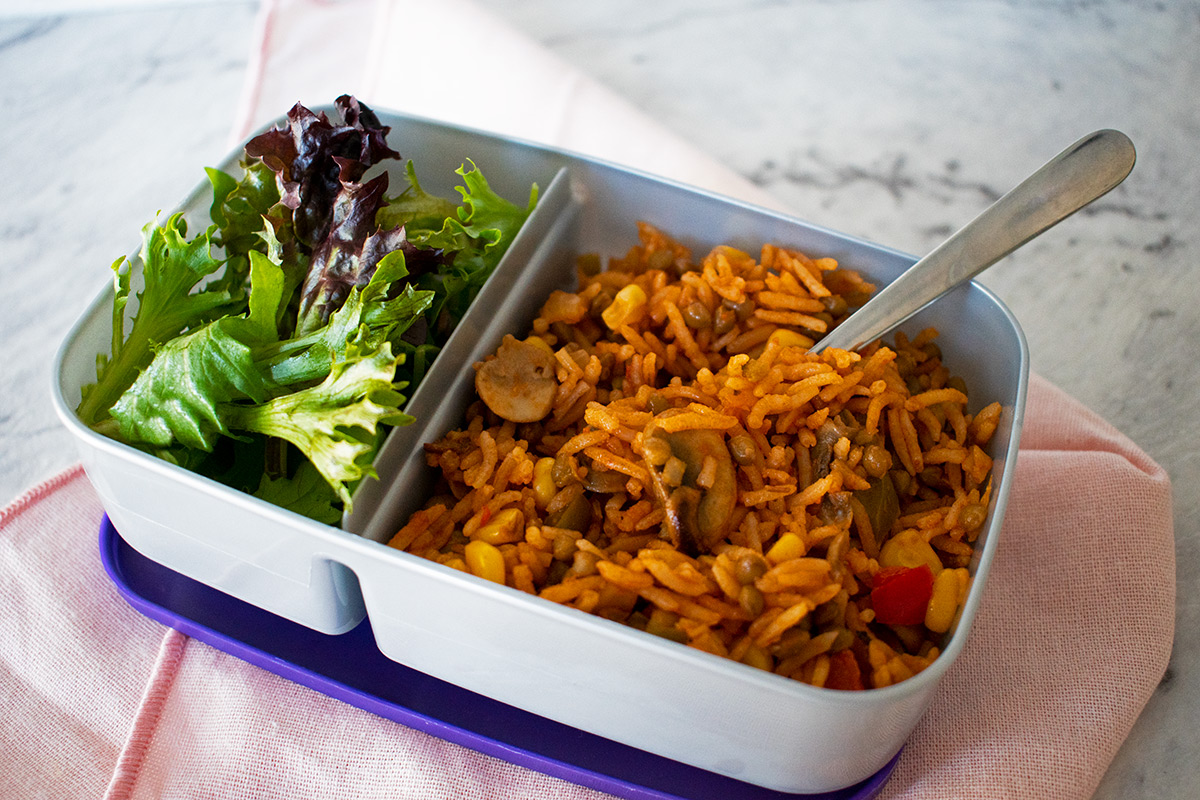 arroz con verduras en una lonchera plastica acompañado de ensalada.