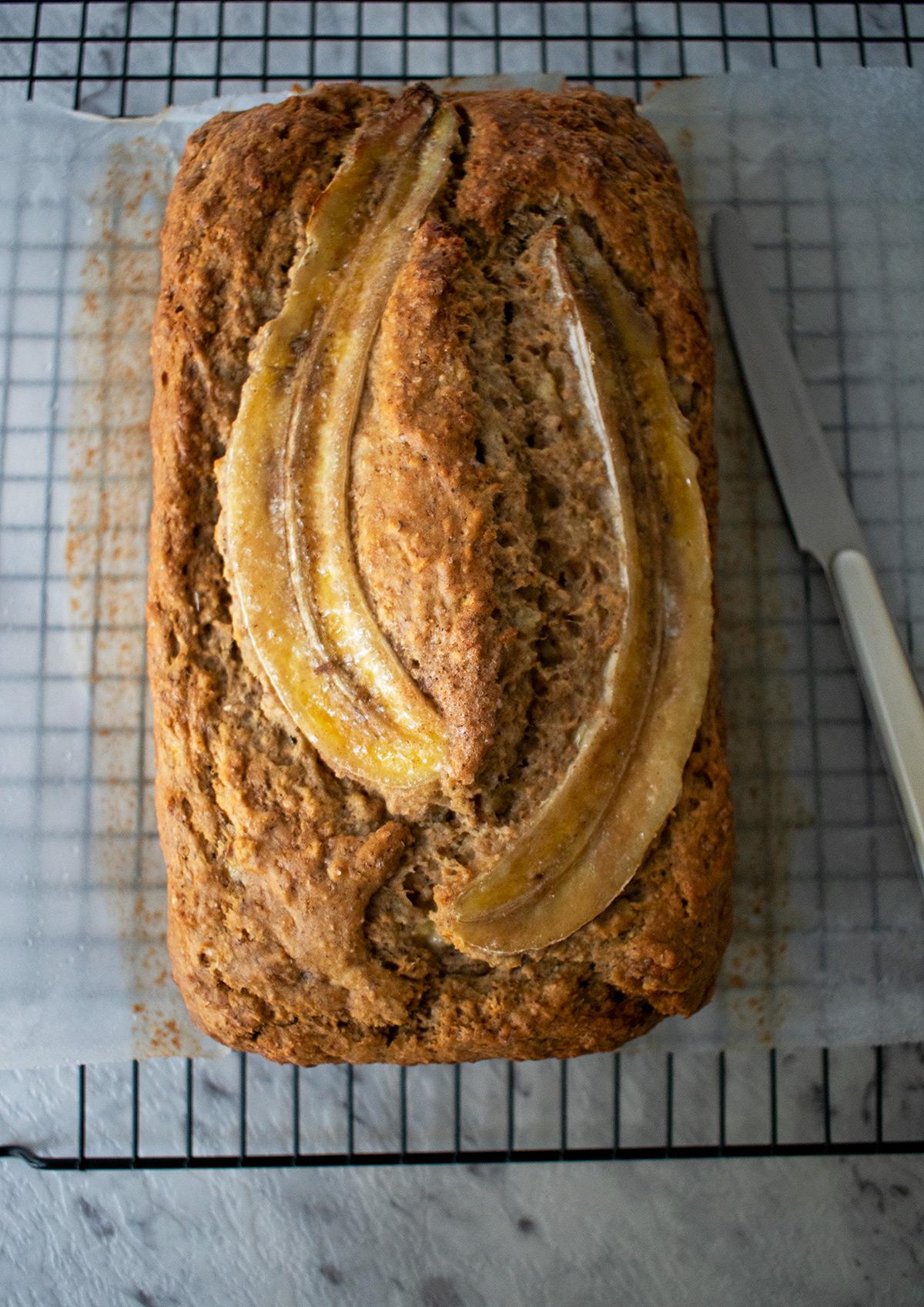 Pan de banana sobre una rejilla con un cuchillo al lado.