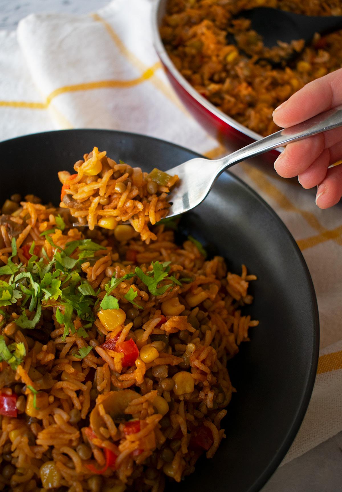 arroz pilaf servido en un plato negro sobre un paño blanco con lineas amarillas