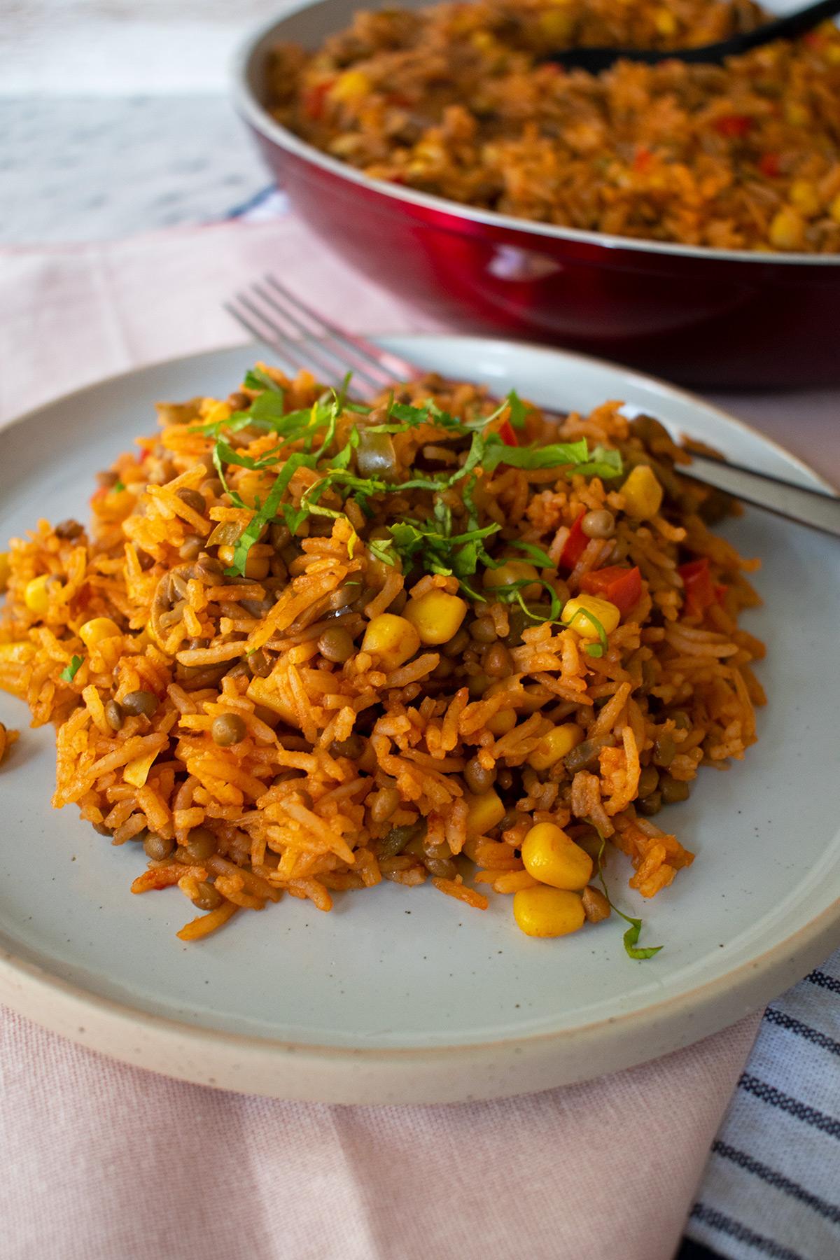 Arroz con verduras servido en un plato redondo con un sartén al fondo.