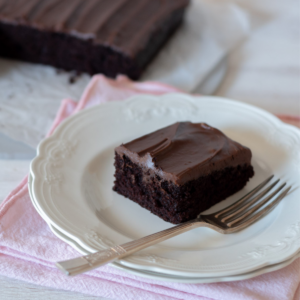 Bizcocho de chocolate sin huevo en un plato blanco con un tenedor al lado.