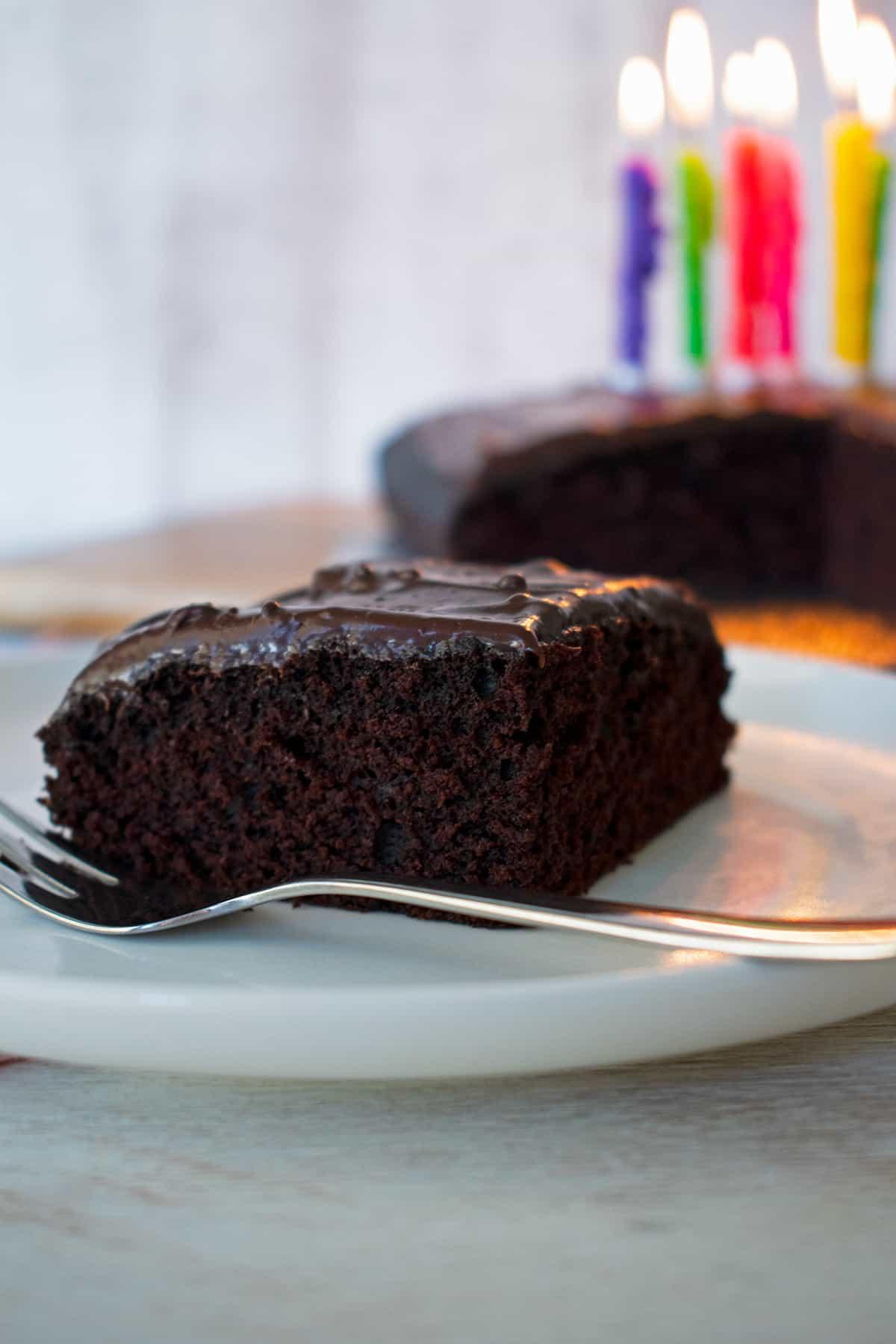 depression cake pastel de depresión en un plato blanco con un tenedor al lado.