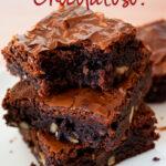 tres brownies super chocolatosos uno sobre otro sobre una mesa blanca