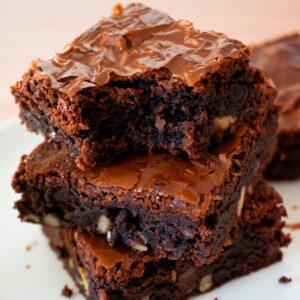 tres brownies caseros uno sobre otro sobre una mesa blanca