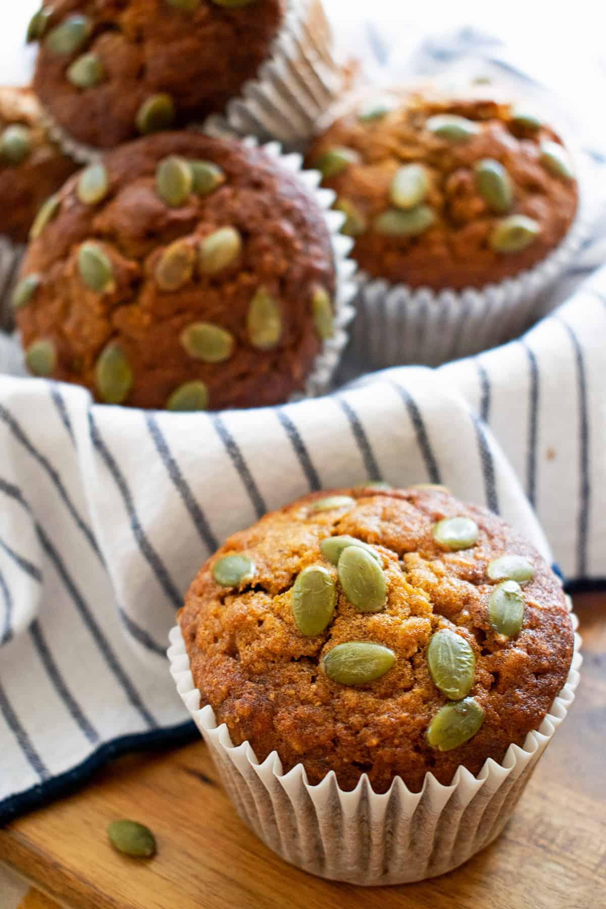 Muffins de calabaza y avena sobre un paño blanco con lineas azules.