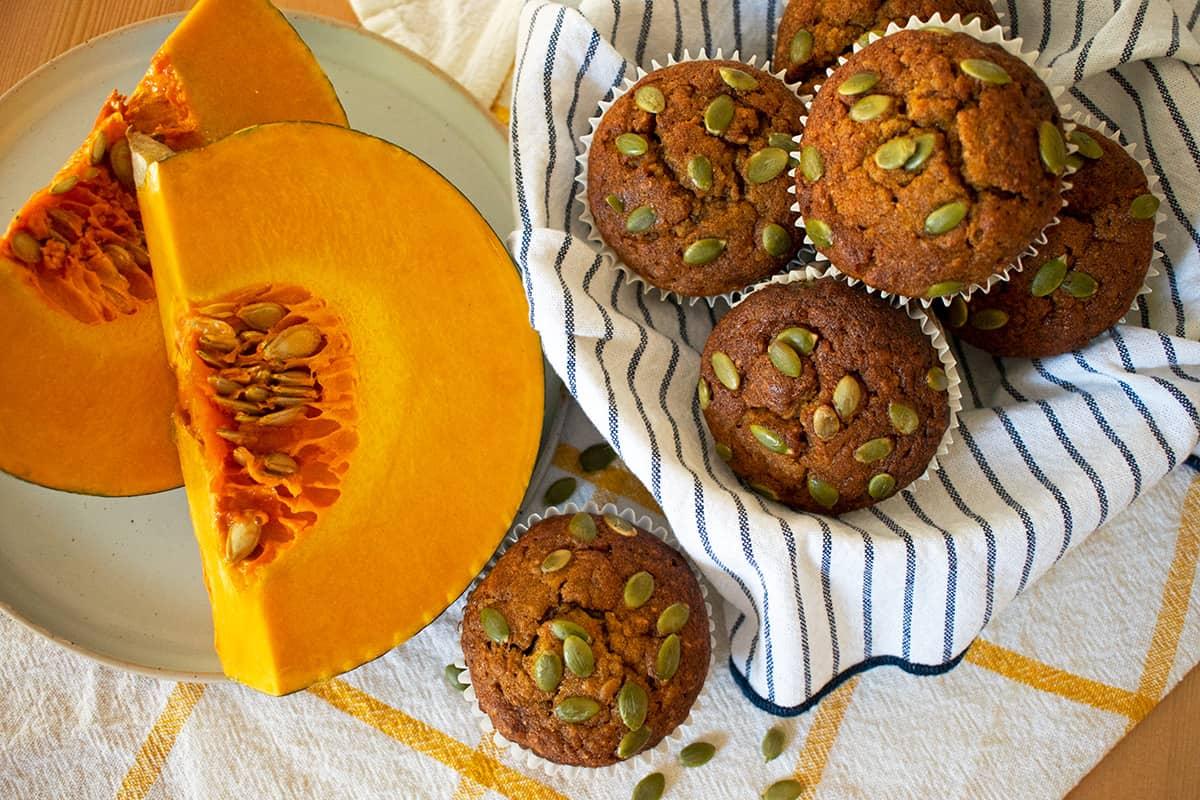 muffins de auyama sobre un paño blanco con lineas azules con media auyama al lado.