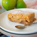 tarta de manzana casera servida en un plato blanco con una pequeña cuchara y tres manzanas verdes detrás