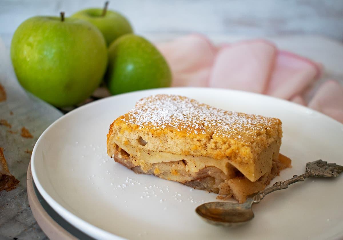 porción de torta mágica de manzana servida en un plato blanco acompañado de 3 manzanas verdes.