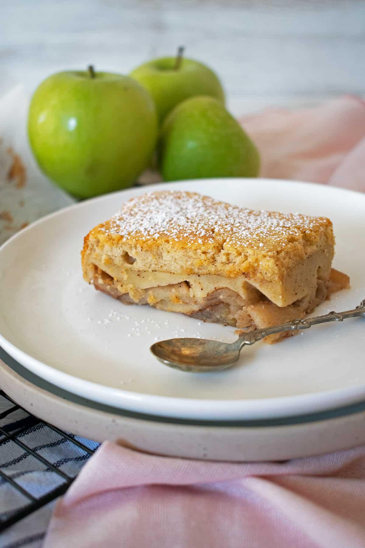 Tarta de manzana servida en un plato blanco con una pequeña cuchara, tres manzanas verdes detrás.