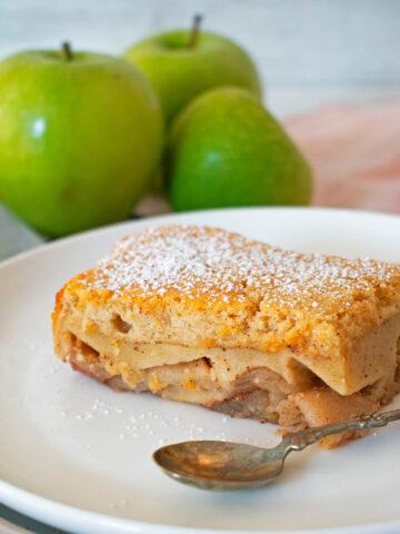 tarta de manzana casera servida en un plato blanco con tres manzanas verdes atrás.