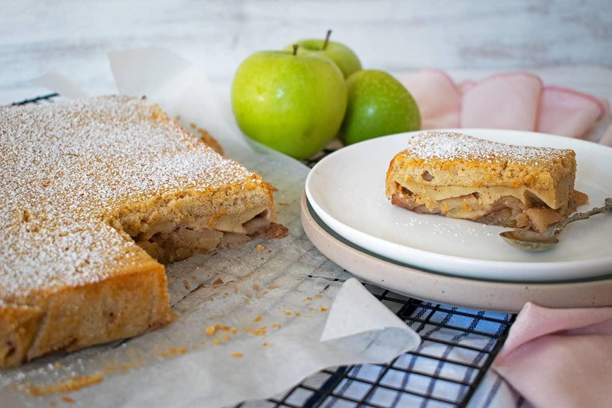 Tarta de manzana sobre una rejilla negra, una porción servida en un plato con una pequeña cuchara y tres manzanas verdes atrás.