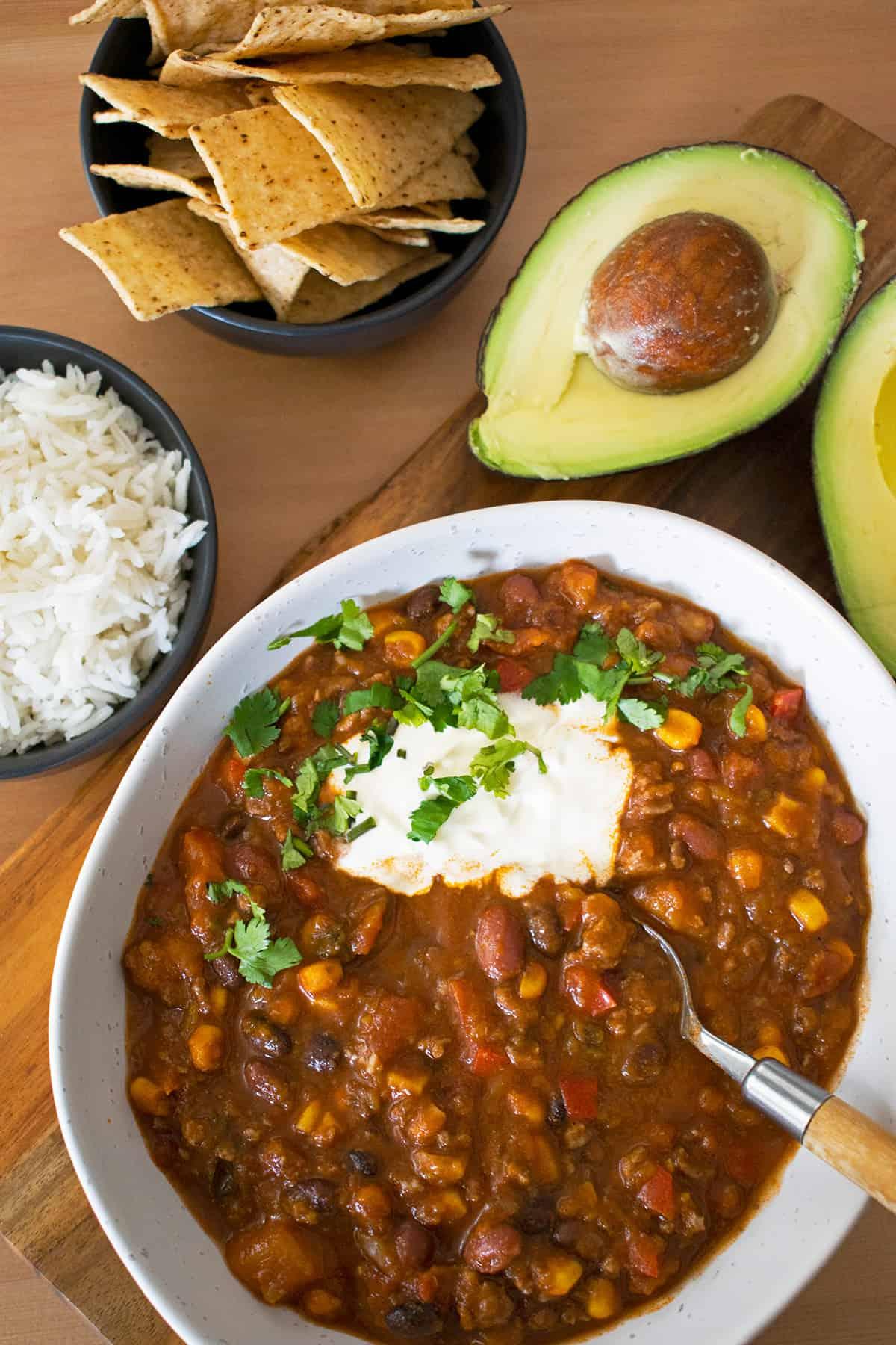 chili con carne acompañado de arroz, chips de maíz y aguacate.