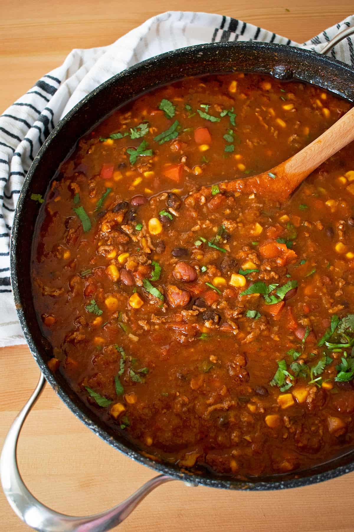 chili con carne casero en una olla grande con una cuchara de madera