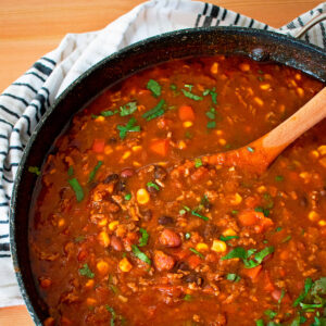 chili con carne en una olla grande con una cuchara de madera