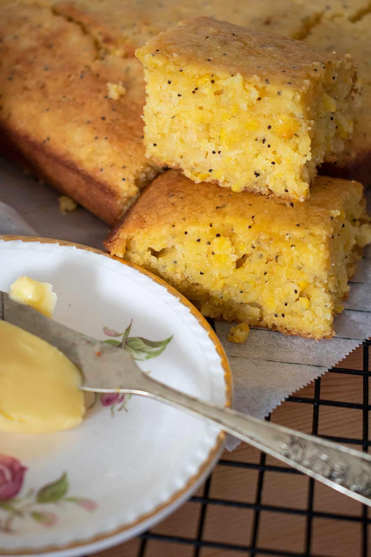 porciones de cornbread sobre una rejilla acompañado de mantequilla en un pequeño plato con flores.
