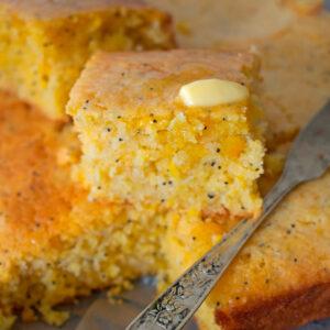 pan de maíz cortado con u poco de mantequilla acompañado de un cuchillo pequeño.