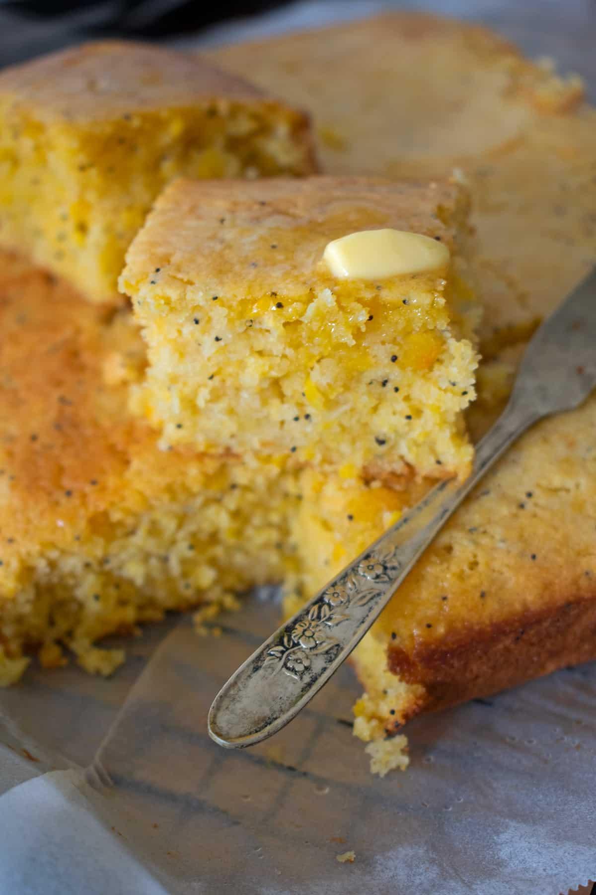 pan de maíz cortado en porciones con un poco de mantequilla acompañado de un cuchillo pequeño.