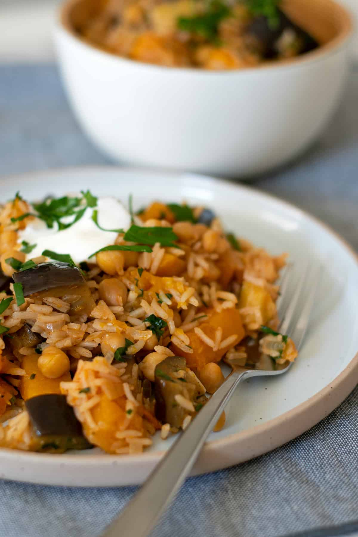 arroz con garbanzos y verduras servido en un plato redondo con un tenedor