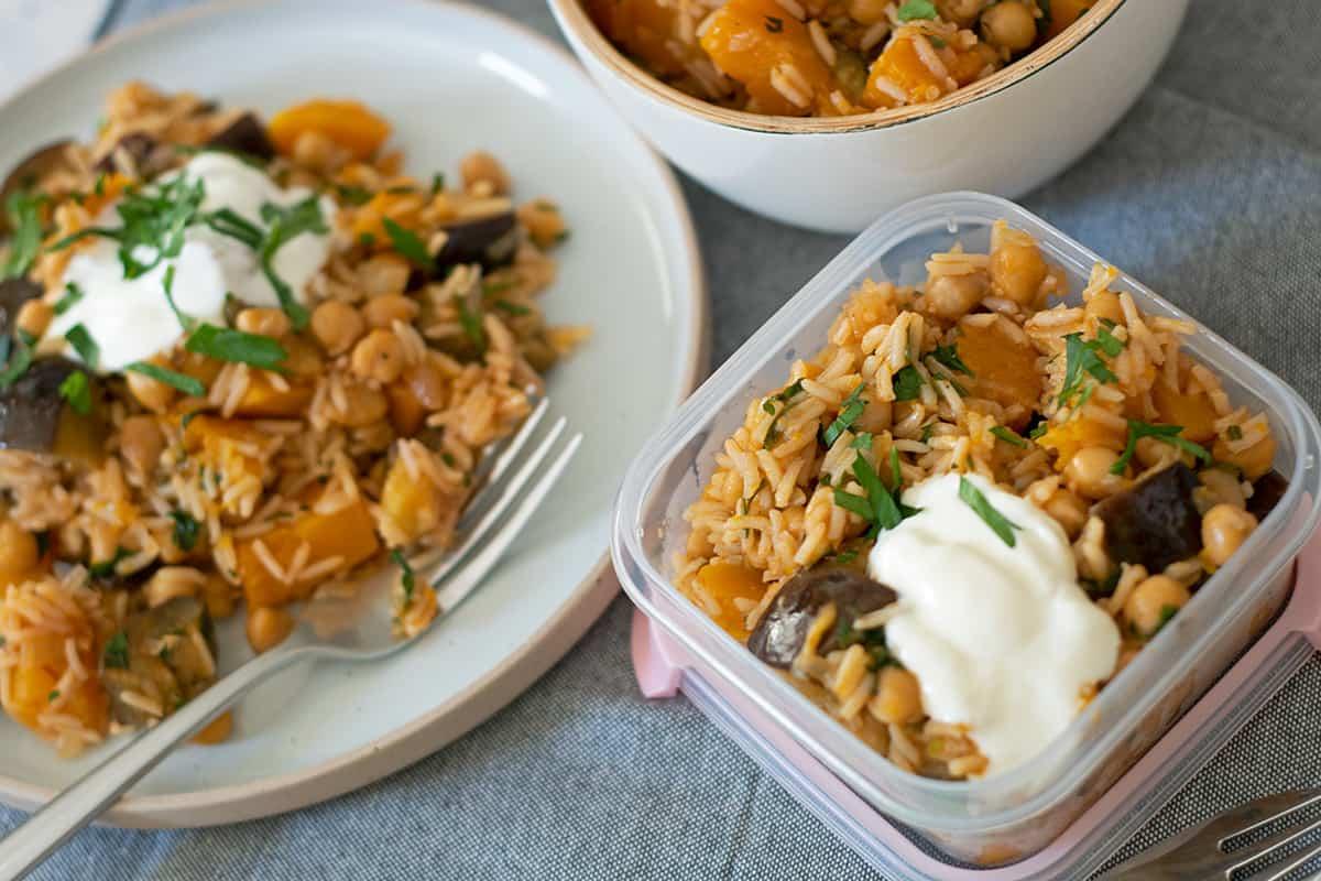 arroz con garbanzos y berenjena servido de tres maneras. en un plato redondo, un bol blanco y un contenedor plástico para llevar.