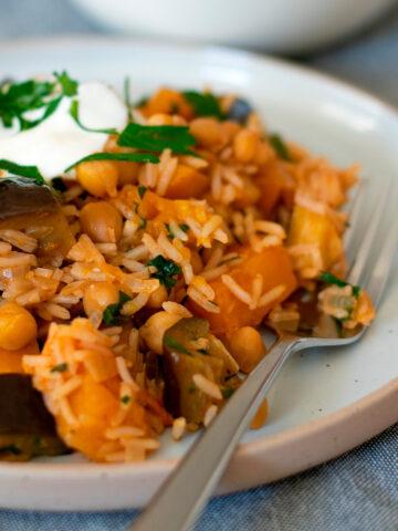 arroz con garbanzos servido en un plato redondo con un tenedor
