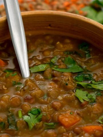 sopa de lentejas servida en un bol con una cuchara platead