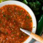 salsa fresca estilo mexicano servida en un plato redondo blanco con una cuchara de madera