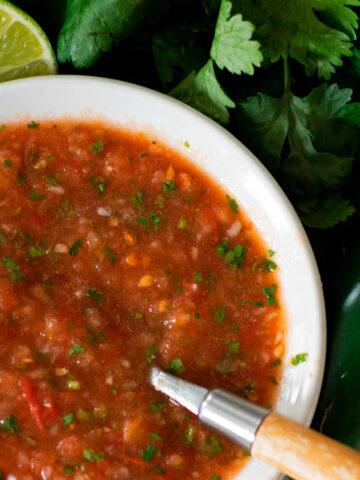 salsa fresca servida en un plato blanco con una cuchara de madera