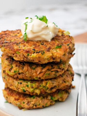 croquetas de quinoa y atún servidas una sobre otra servidas sobre un plato blanco.