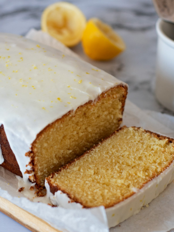 torta de limón casera servida sobre una tabla de madera acompañada por un tenedor plateado