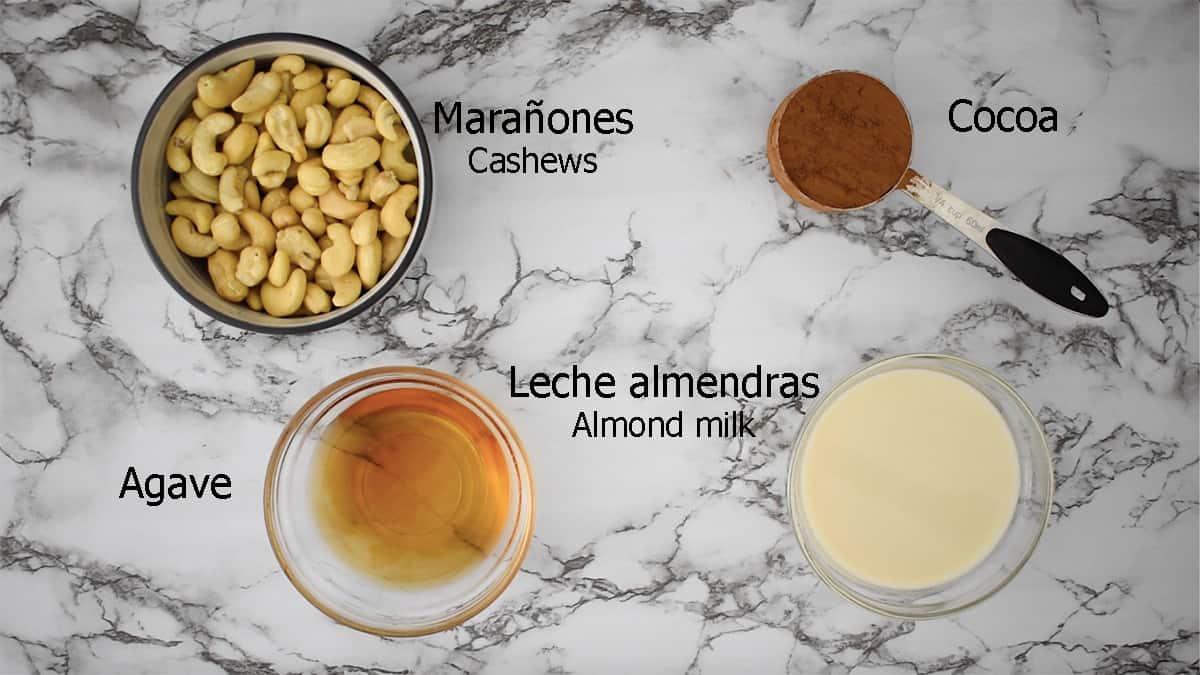 ingredientes para preparar crema de cacao vegana. marañones, cocoa, agave y leche de almendras