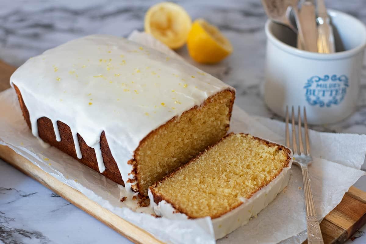 Bizcocho de limón casero con glaseado servido sobre una tabla de madera acompañado de un tenedor plateado