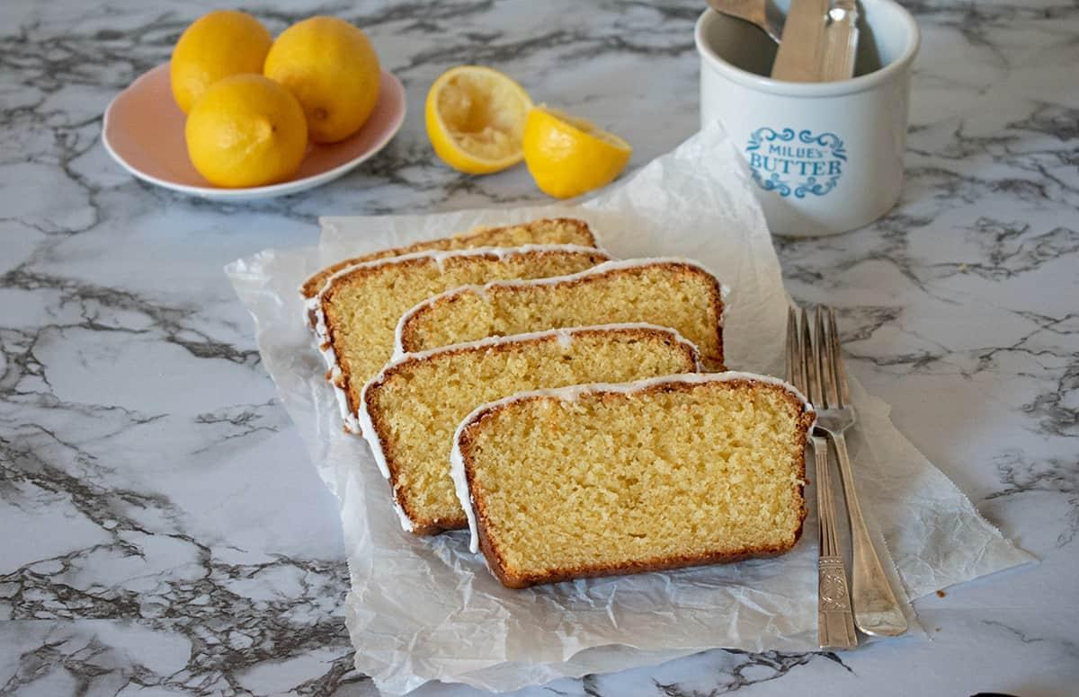 porciones de torta de limón servidas sobre una superficie de mármol acompañadas por dos tenedores plateados con tres limones en la parte de atrás servidos en un pequeño plato rosado.