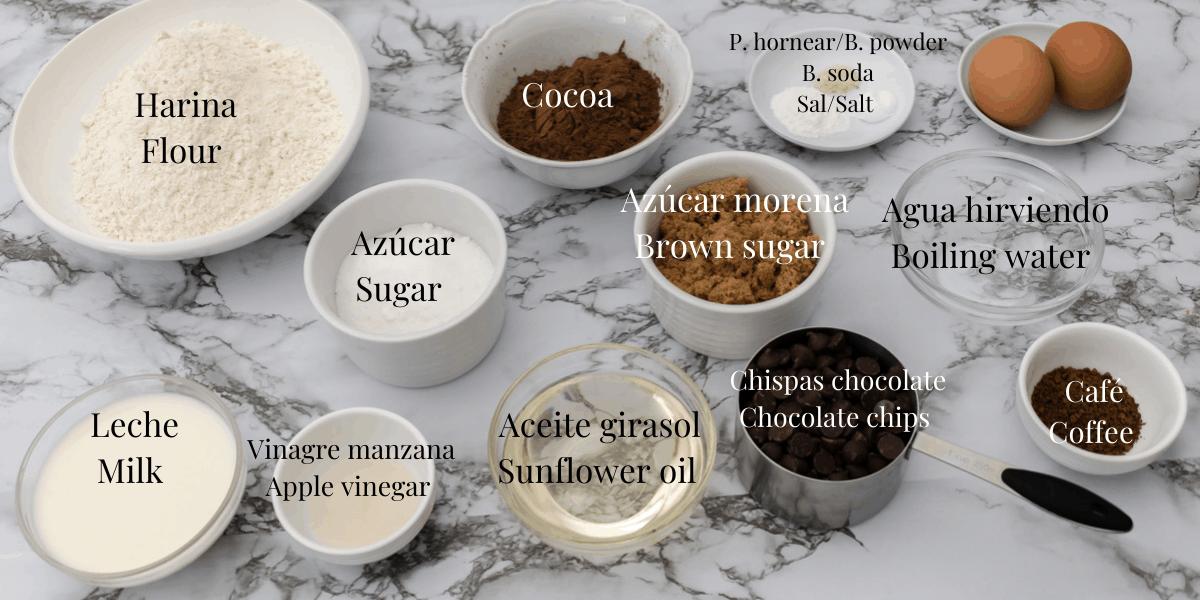 Ingredientes para preparar muffins de chocolate. Harina de trigo, cocoa, azúcar blanca y azúcar morena, café, aceite de girasol, leche, vinagre de manzana, aceite de girasol, chispas de chocolate, huevos, polvo de hornear, sal y bicarbonato de soda.