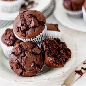 muffins de chocolate servidos en un plato redondo sobre una mesa blanca.