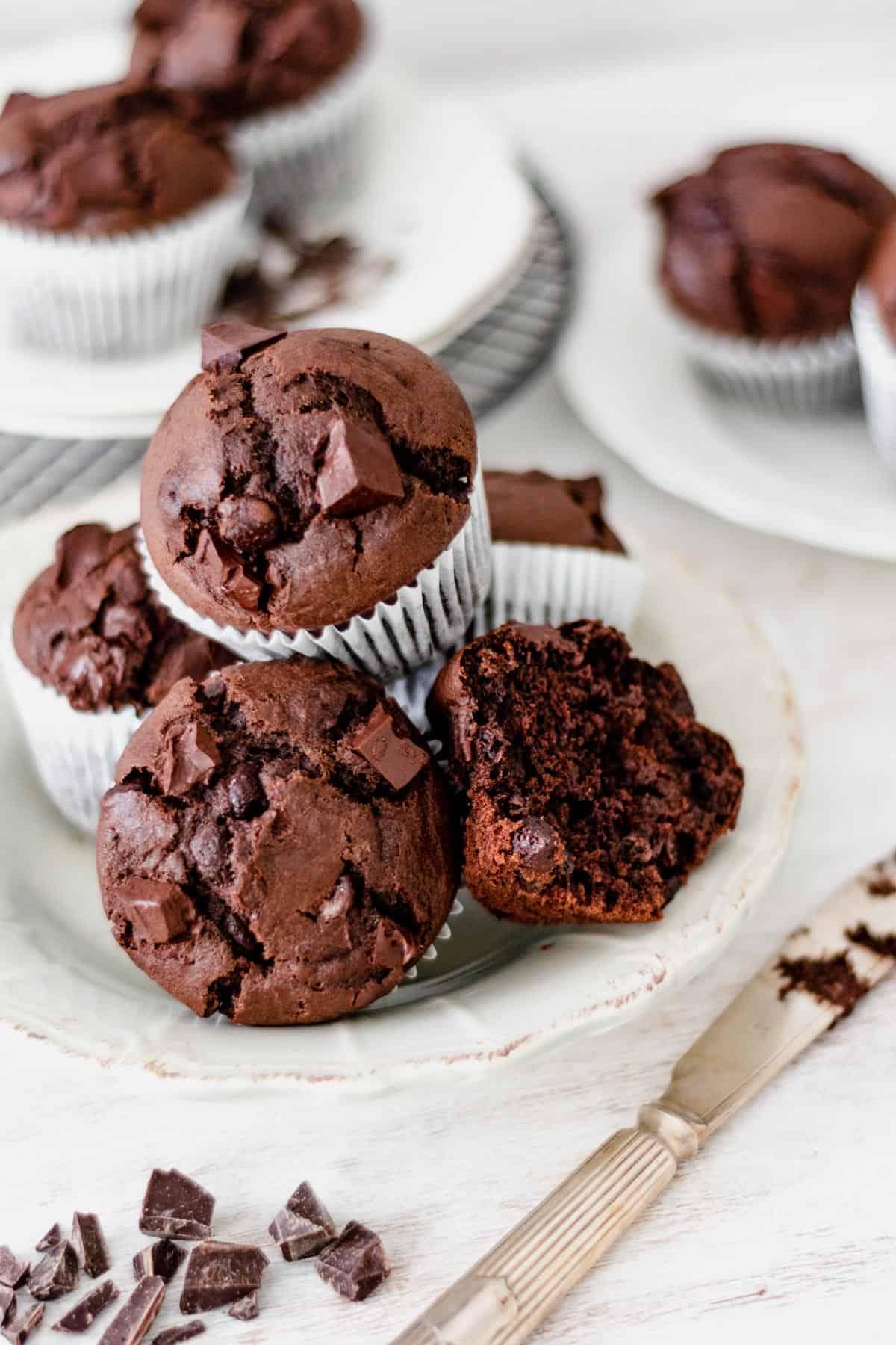 Muffins de chocolate servidos en un plato redondo con un cuchillo plateado al lado.